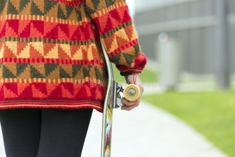 Main de plan rapproché tenant la planche à roulettes, concept urbain de mode de vie photographie stock