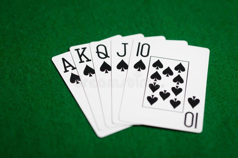 Main de poker de jouer des cartes sur le tissu vert de casino image stock