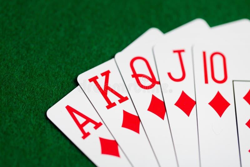 Main de poker de jouer des cartes sur le tissu vert de casino photos stock