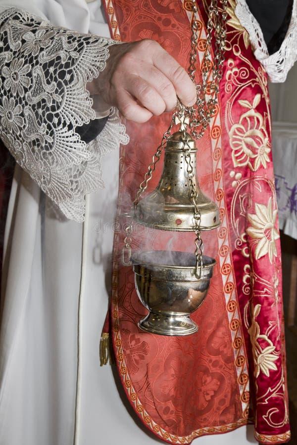 Main de prêtre catholique à l'encens image stock