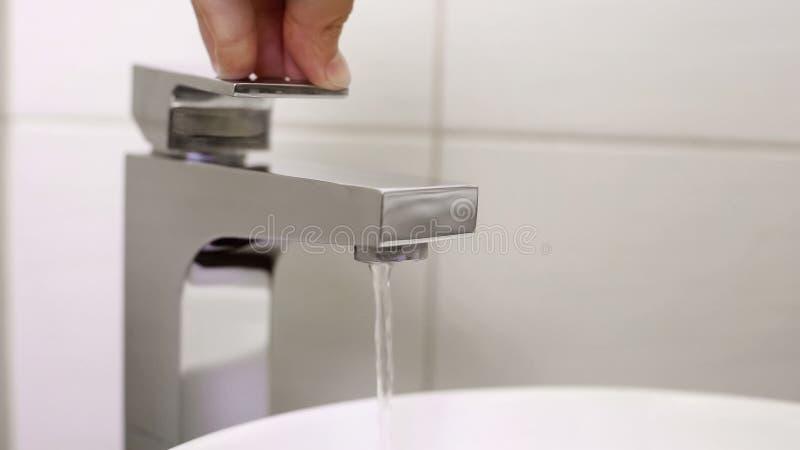 Main de propriétaire vérifiant la reprise d'approvisionnement en eau après le paiement des dettes, utilité photo libre de droits
