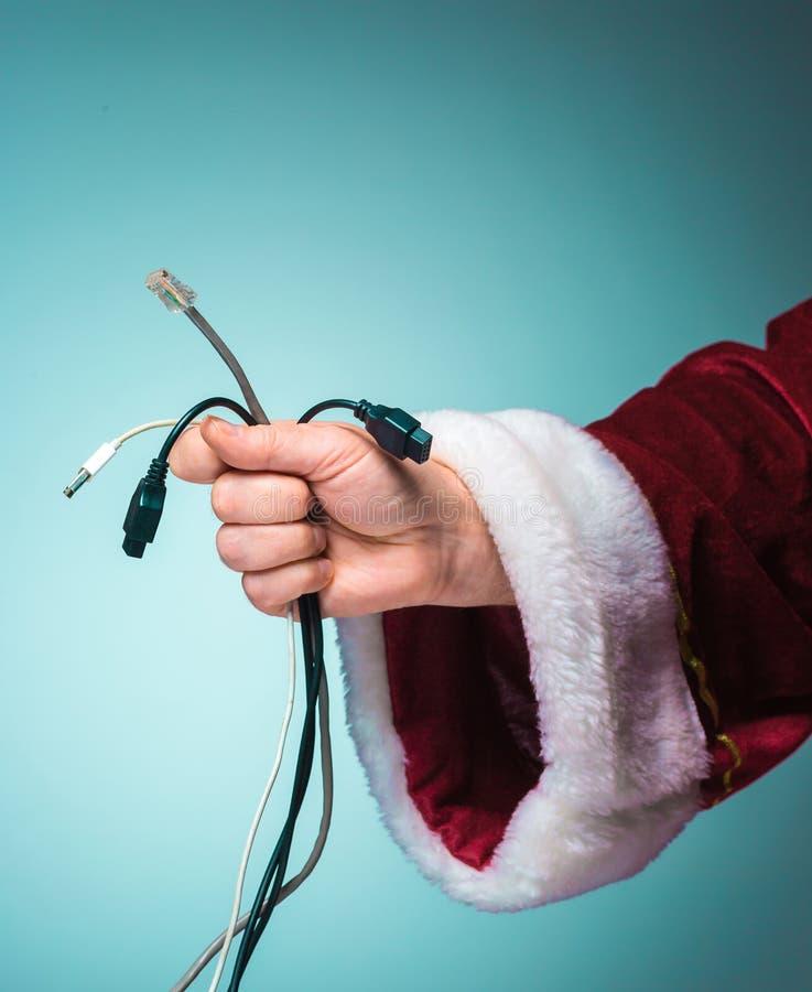 Main de Santa Claus tenant des connecteurs d'un groupe sur des instruments sur le fond bleu image libre de droits