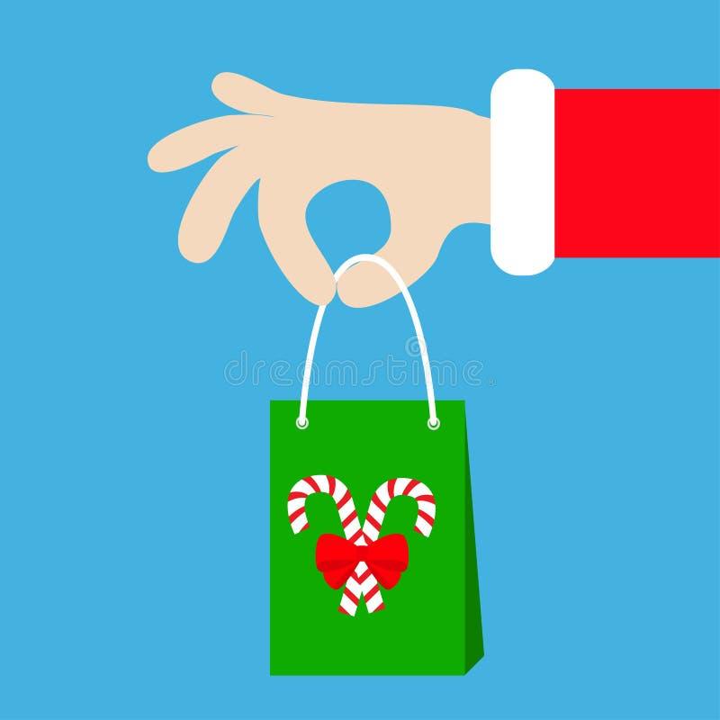 Main de Santa Claus tenant le sac de papier de achat de cadeau avec la canne de sucrerie Joyeux Noël Fourrure rouge de costume Do illustration libre de droits