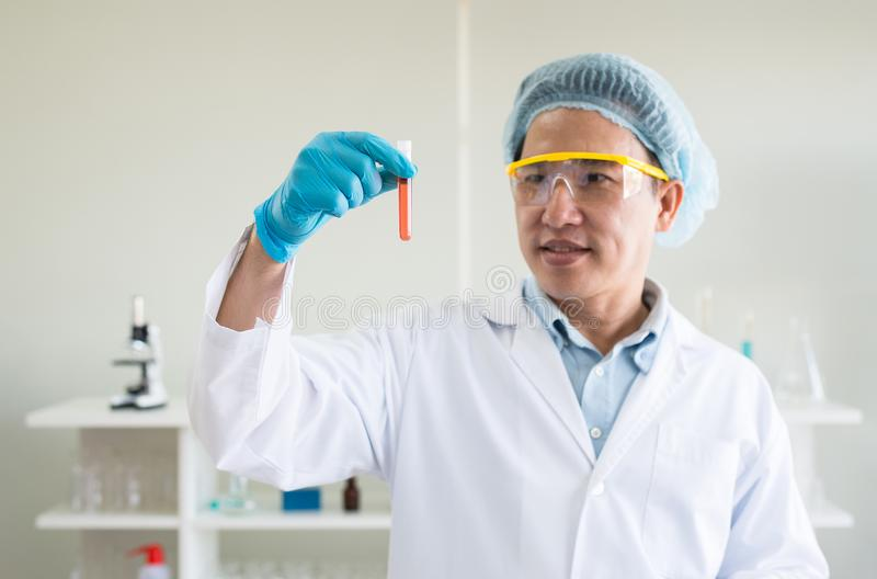 Main de scientifique tenant l'échantillon médical de produits chimiques dans le tube à essai avec la prise de sang photographie stock