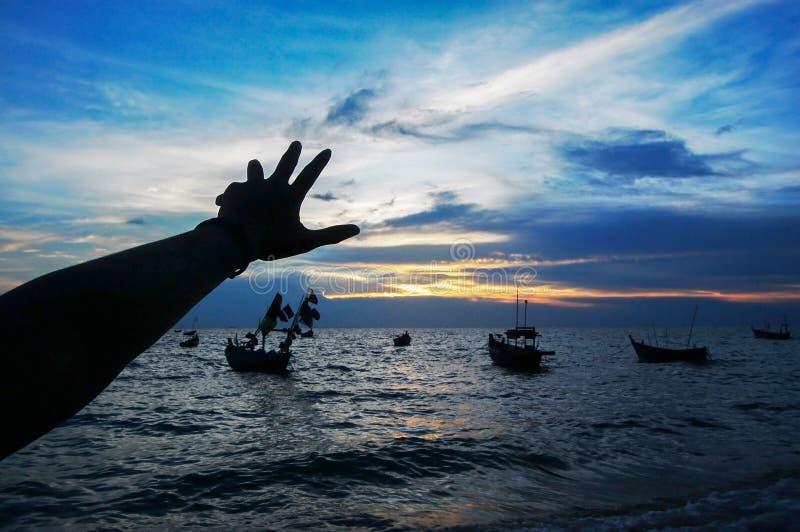 Main de Silhiuette grapping avec la plage au coucher du soleil photo stock