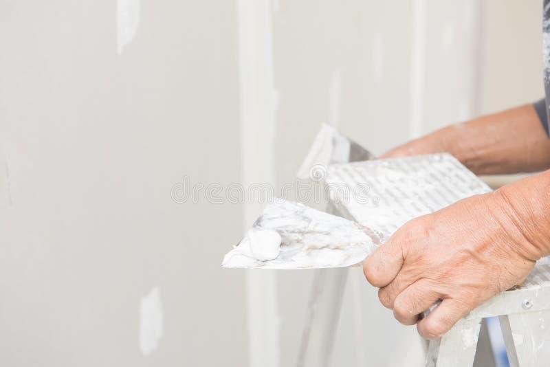Main de travailleur avec le plâtre et la truelle au panneau de gypse photos libres de droits