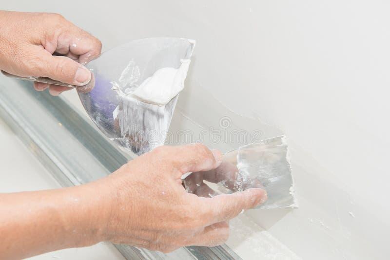 Main de travailleur avec le plâtre et la truelle au panneau de gypse image stock