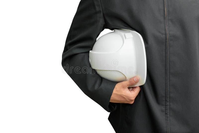 Main de travailleur d'ingénierie jugeant le casque de sécurité blanc en plastique dans la construction d'isolement sur le fond bl images libres de droits