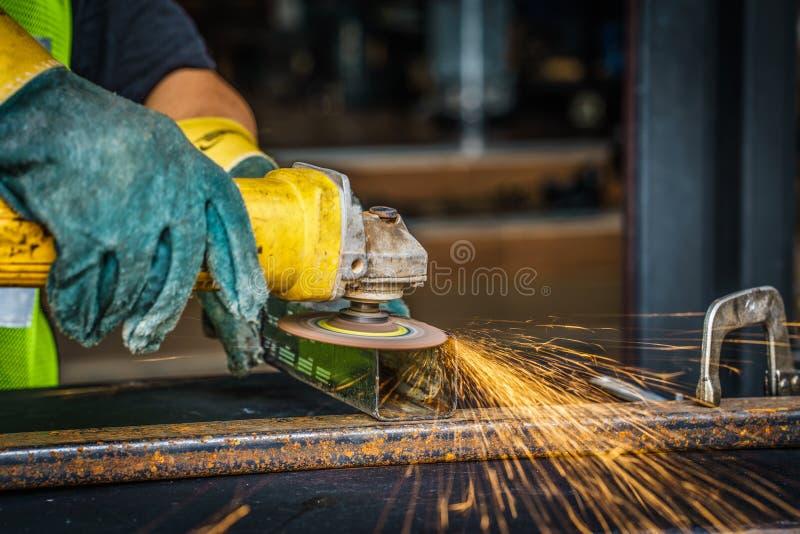 Main de travailleur fonctionnant à côté de l'outil électrique d'industrie de broyeur coupant le St photos libres de droits