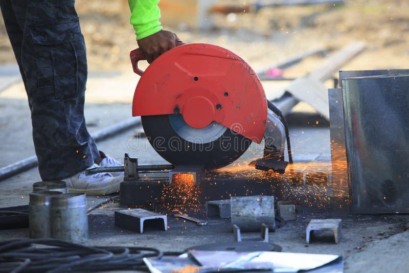 Main de travailleur fonctionnant à côté de l'outil d'industrie coupant l'acier avec la fente fi photo stock