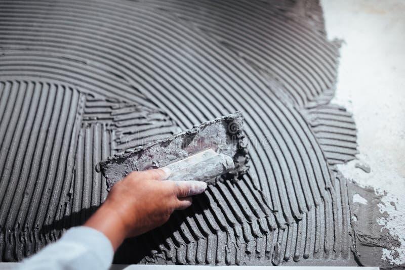 Main de travailleur plâtrant un mur, ajoutant l'adhésif avec la truelle de peigne photo stock