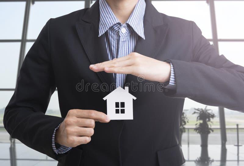 Main de vendeur d'affaires tenant l'assurance à la maison images stock
