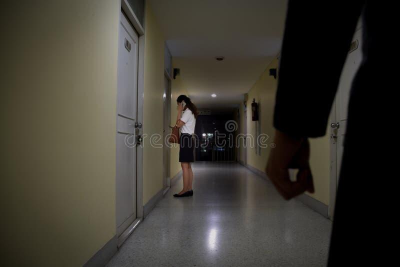 Main de voleur ou de voleur regardant à la femme d'affaires qui utilisant le mobile la porte la nuit, foyer sur des personnes, co images libres de droits