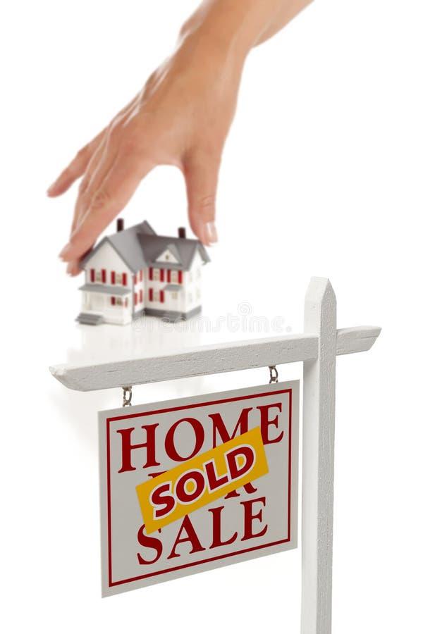 Main de Womans choisissant à la maison, signe vendu d'immeubles photos libres de droits