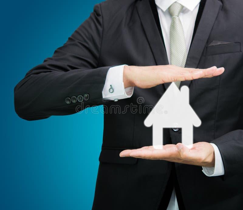 Main debout de posture d'homme d'affaires tenant l'icône de maison images stock
