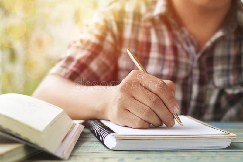 Main des personnes, de l'écriture d'étudiant et de la note sur le carnet sur la table en bois avec l'espace de copie, dans la bib photographie stock libre de droits