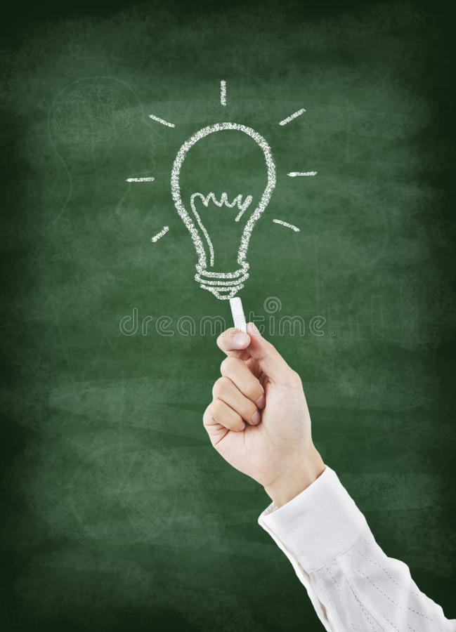 Main dessinant l'ampoule sur le tableau illustration stock