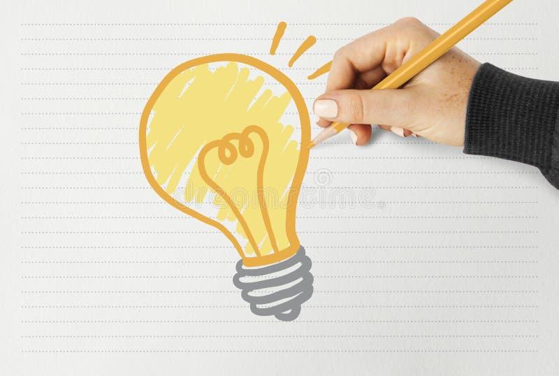 Main dessinant une ampoule sur un papier photographie stock libre de droits