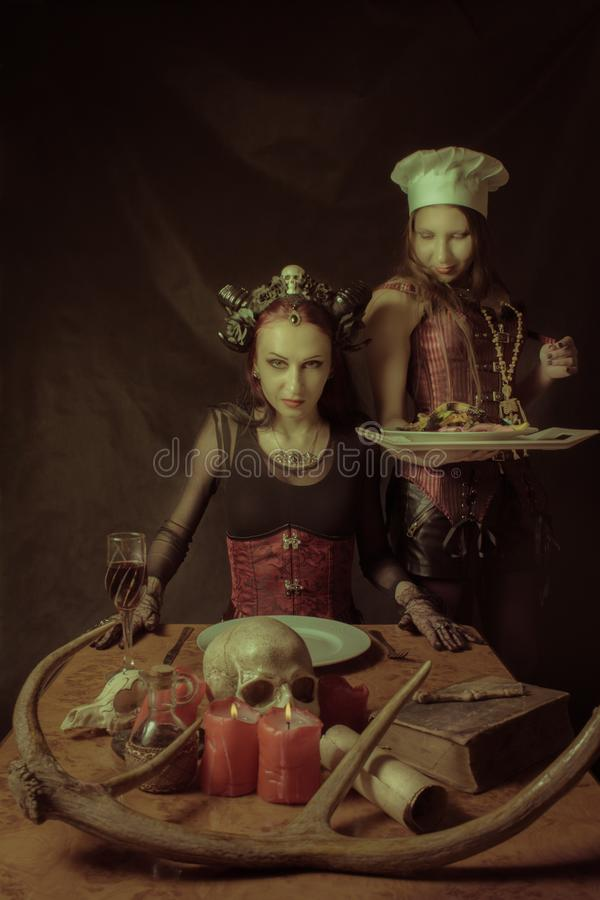 Main dish for Satan. Cook with main dish and her horned lord over dark background stock photography
