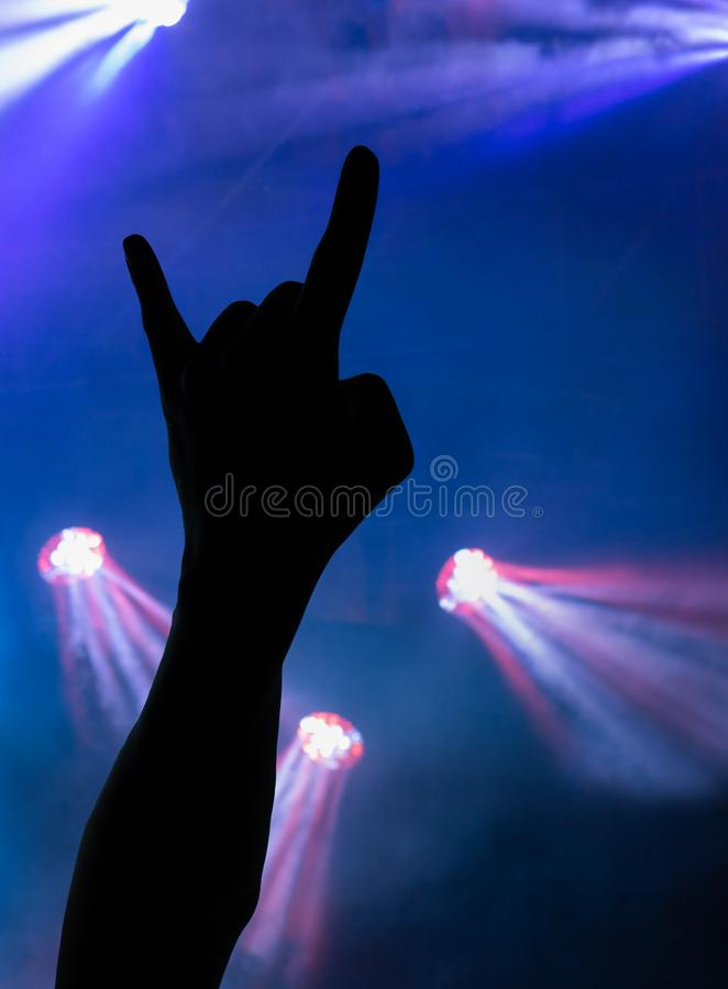 Main donnant la roche pendant le concert image stock
