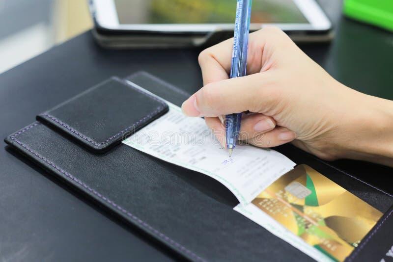 Main du consommateur se connectant un reçu de transaction de vente avec le crédit images stock