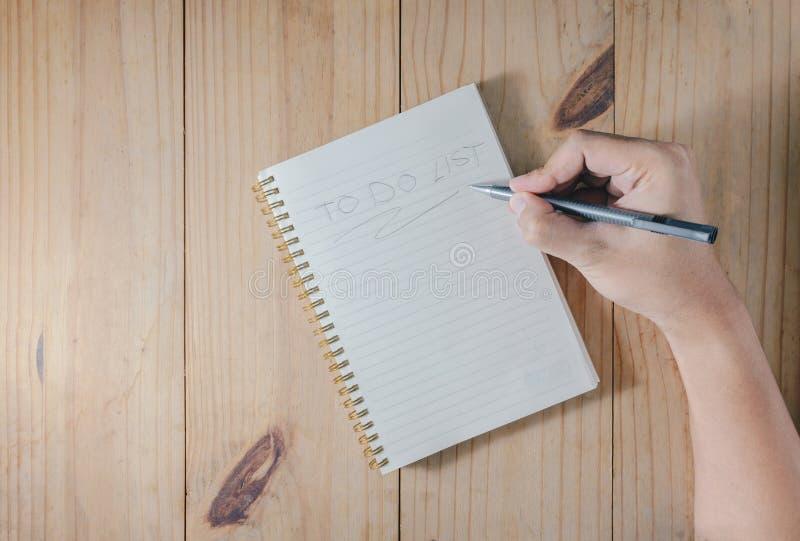 Main du ` d'écriture de crayon d'utilisation de l'homme POUR FAIRE le ` de LISTE sur le carnet blanc sur la table en bois photo libre de droits