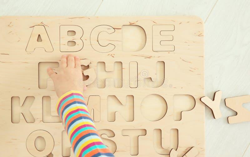 Main du petit enfant mignon jouant avec des lettres images stock