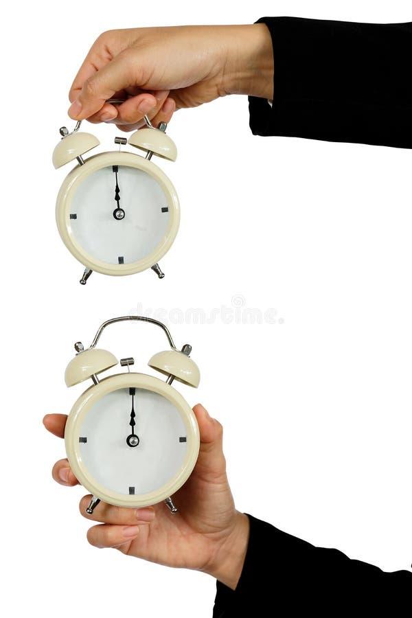 Main du réveil de prise d'affaires avec l'apparence 12 heures d'isolement sur blanc - concept de temps image libre de droits