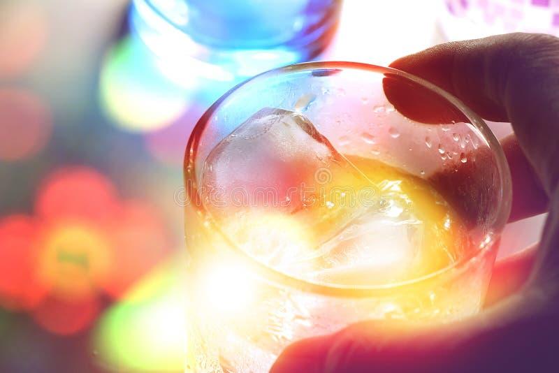 Main du ` s d'homme tenant un verre de boisson d'alcool avec des glaçons photographie stock libre de droits