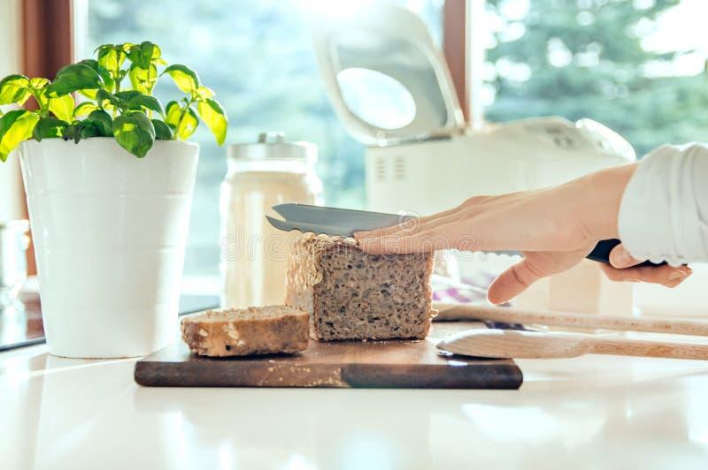 Main du ` s de femme avec le couteau de cuisine coupant le pain sain fait maison photos stock