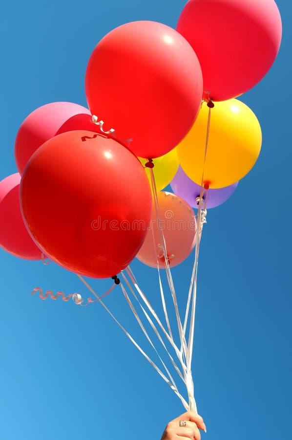 Main du ` s de femme tenant le groupe de ballons multicolores image stock