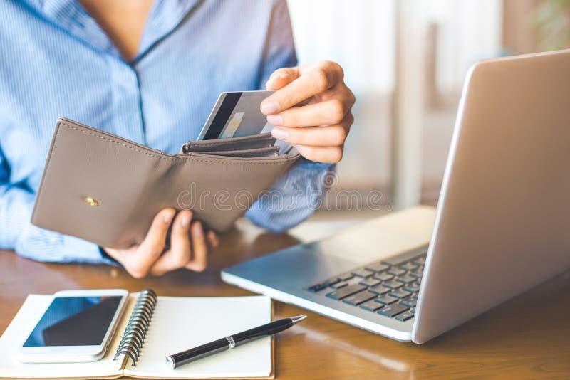 Main du ` s de femmes utilisant une carte de crédit, elle a tiré la carte hors de elle photos libres de droits