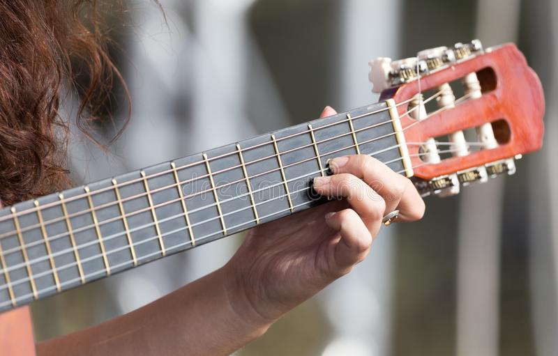 Main du ` s de fille jouant la guitare photo stock