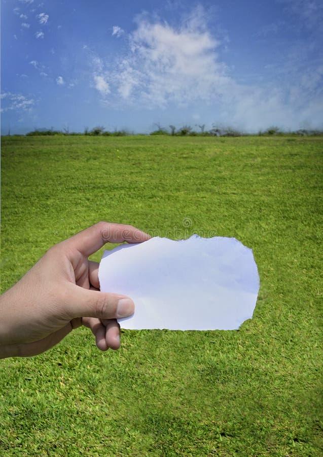 Main du ` s de jeune homme tenant le papier blanc Ciel bleu photographie stock