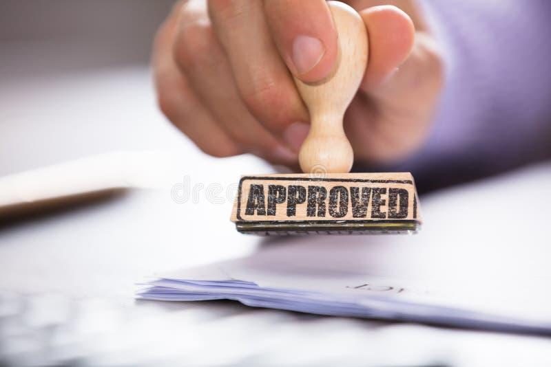Main du ` s de personne tenant le timbre approuvé sur le document image stock