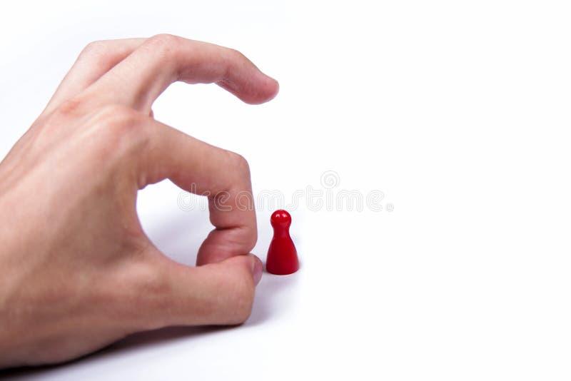 Main effleurant un seul morceau rouge de jeu sur le fond blanc, ?limination images libres de droits