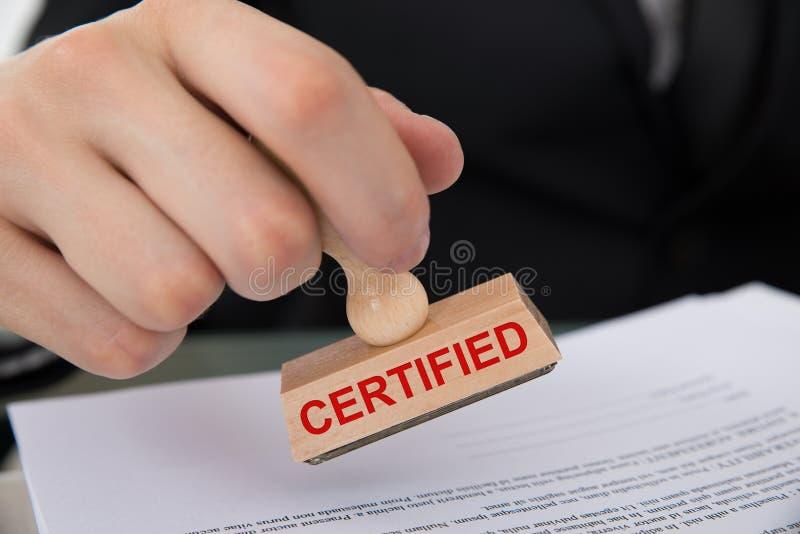 Main emboutissant le document avec le tampon en caoutchouc certifié photographie stock