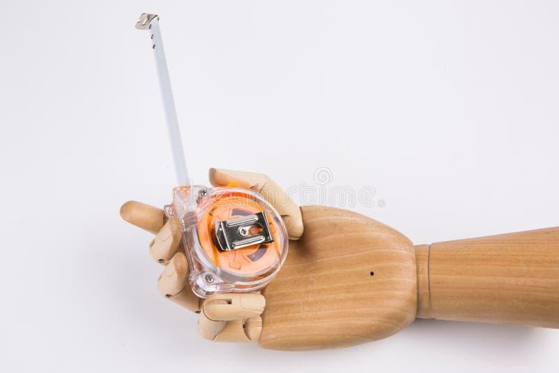 Main en bois tenant la roulette de construction images stock