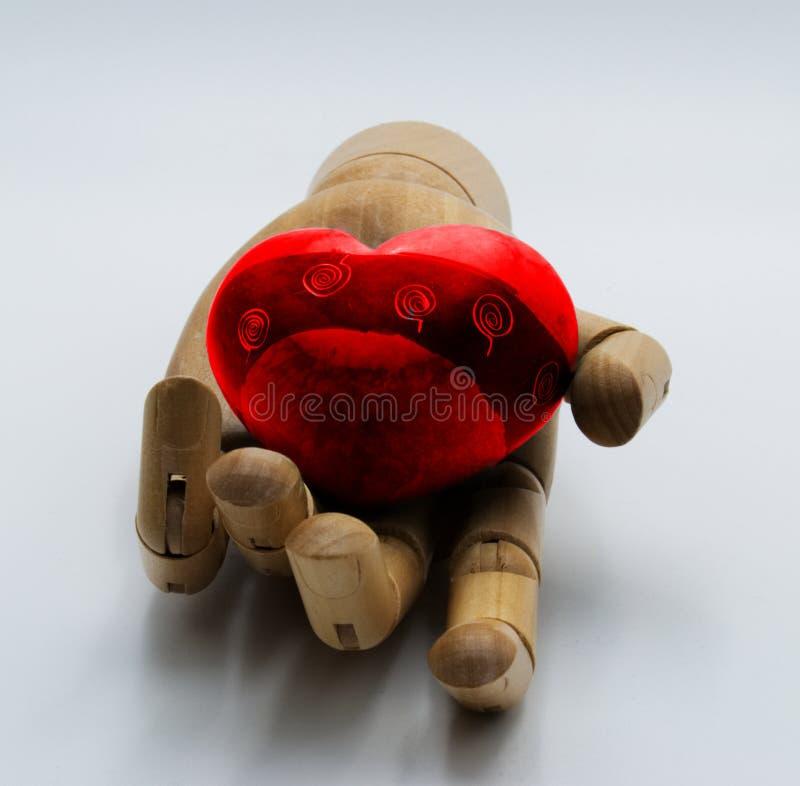 Main en bois tenant un coeur rouge photos stock