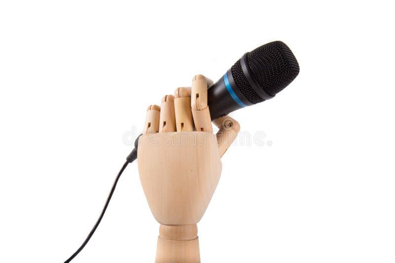 Main en bois tenant un microphone images stock