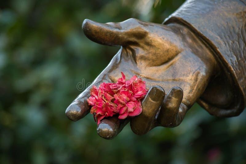 Main en bronze de statue tenant des fleurs photo libre de droits