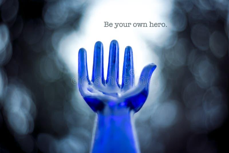 Main en verre bleue atteignant jusqu'au ciel avec l'énonciation photographie stock libre de droits