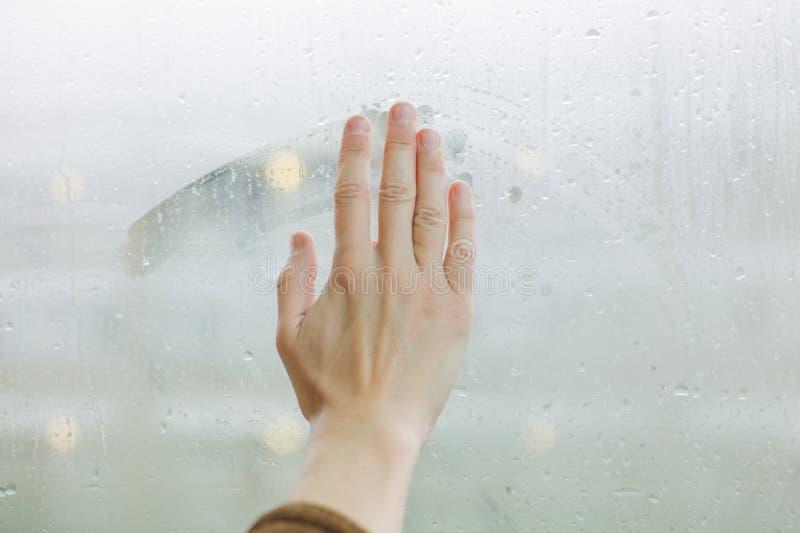 Main essuyant la rosée outre de la fenêtre images stock