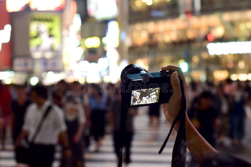 MAIN ET APPAREIL-PHOTO CONQUÉRANT LA VILLE OCCUPÉE LA NUIT photo libre de droits