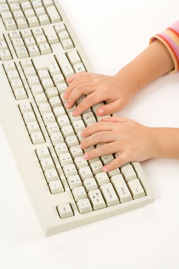Main et clavier d'enfant photographie stock libre de droits