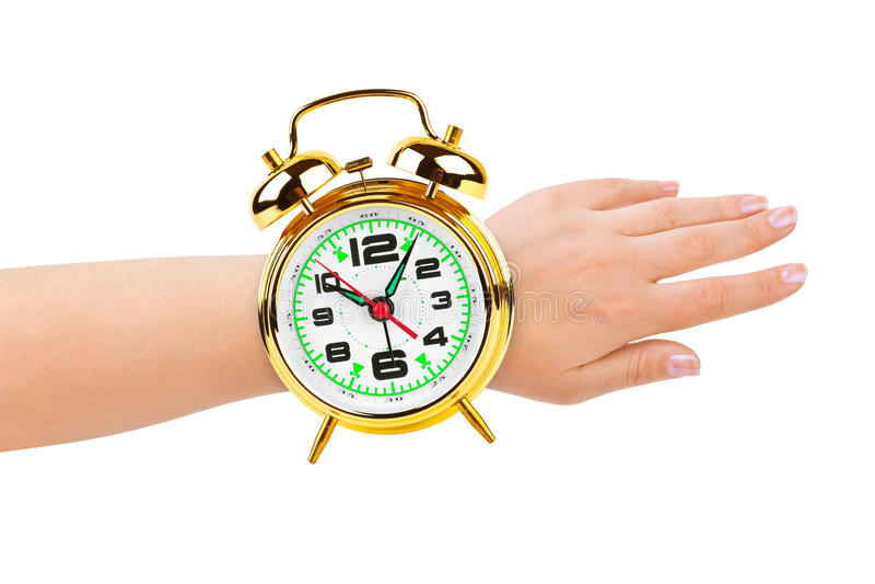 Main et horloge d'alarme comme une montre image stock