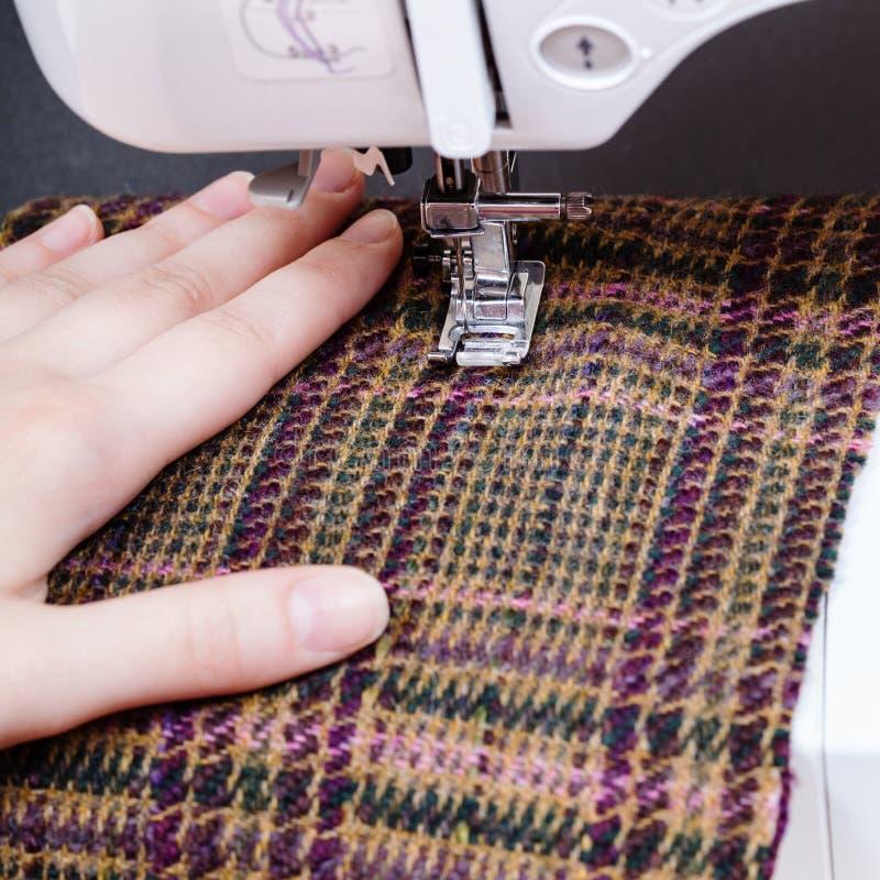 Main et pied de machine à coudre sur le tissu de laine photographie stock libre de droits