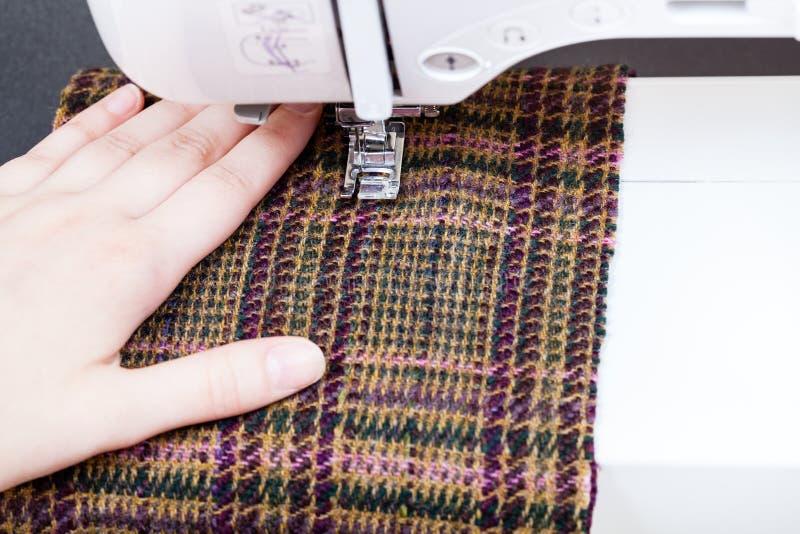 Main et pied de machine à coudre sur le tissu de laine photo libre de droits
