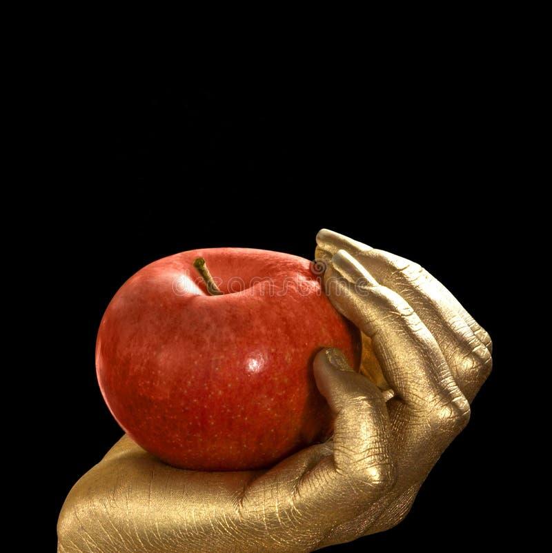 Main et pomme d'or images stock
