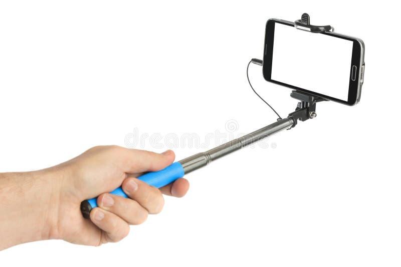 Main et smartphone avec le bâton de selfie photographie stock